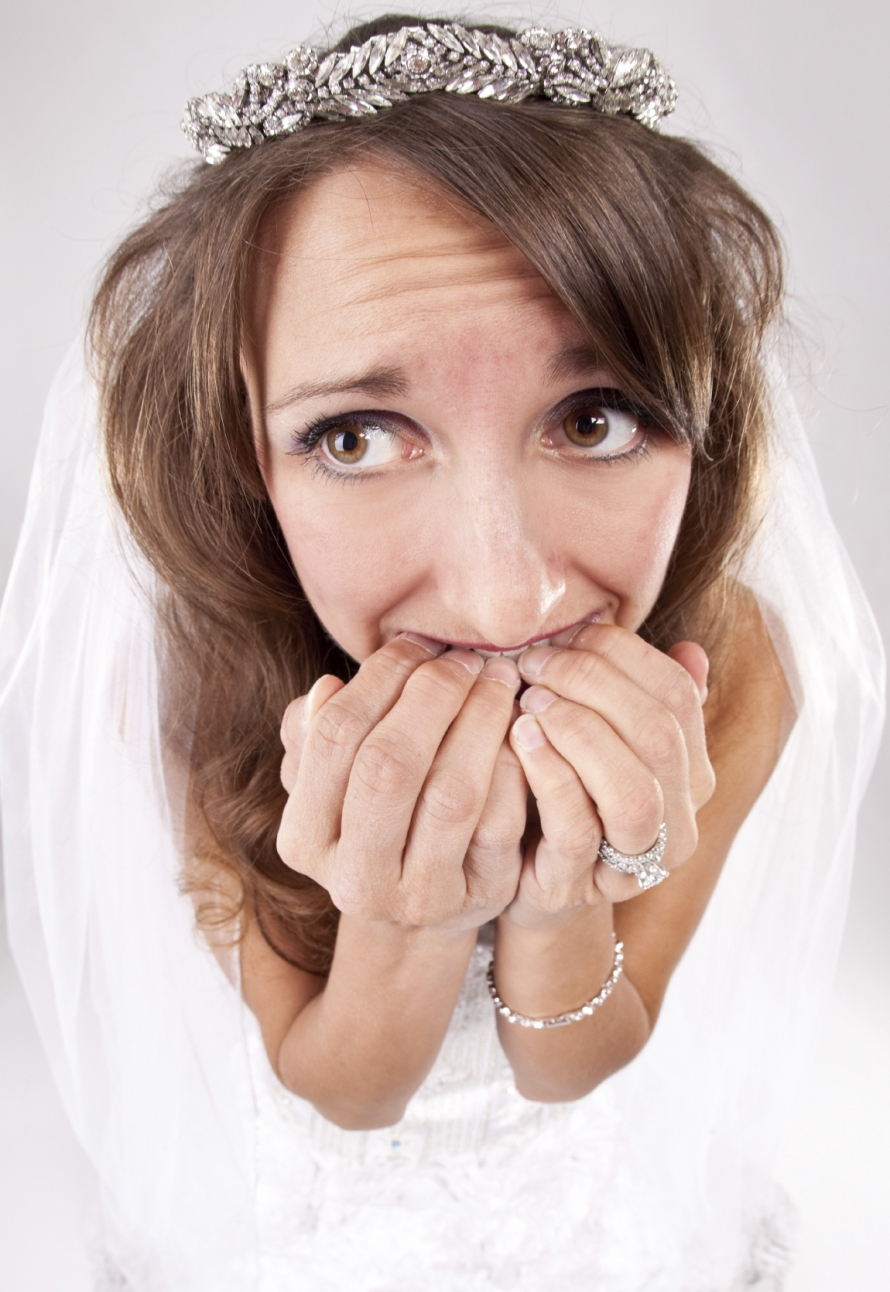 A nervous bride biting her fingernails.